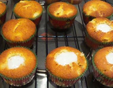 Muffins auf einem Rost. Einge sind mit einer wießen Creme in der Mitte gefüllt.